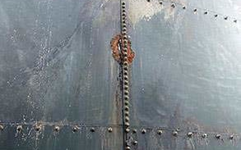Corroded and holed storage tank wall