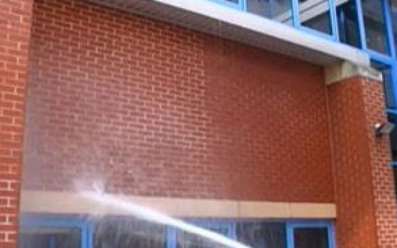 Demonstration of the water repellent properties of Belzona 5122 (Clear Cladding Concentrate) on the left side of the wall